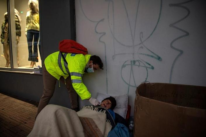 A nurse in Athens takes a swab from a homeless man for an antigenic test as Greece faces a new wave of Covid-19 infections