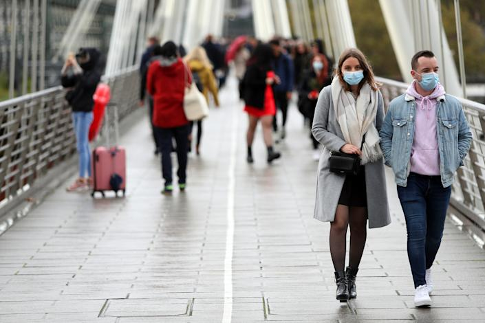 A couple wearing face masks keep on their side of the Golden Jubilee Bridge in London as the UK heads for another lockdown due to coronavirus.