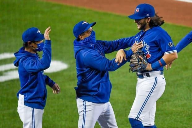 Blue Jays manager Charlie Montoyo, centre, and shortstop Bo Bichette, right, celebrate a win in September. Radio listeners will hear Sportsnet's TV feed of the game  (Adrian Kraus/The Associated Press - image credit)
