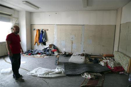 Local Libera leader Corona stands in hall of an abandoned school alongside tin foil used for crack cocaine, a filthy mattress and piles of clothing in Scampia, district of northern Naples