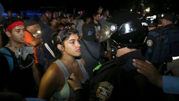 PHOTO: A protester confronts a police officer who is part of a battalion blocking the gate of the Yolanda Guerrero Cultural Center in Guaynabo, Puerto Rico, July 21, 2019. (Pedro Portal/Miami Herald via AP)