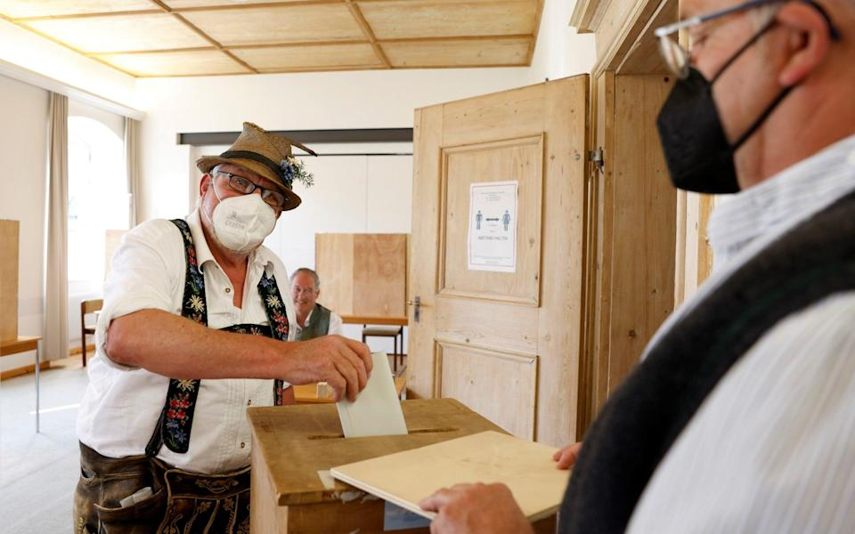 A man wearing traditional Bavarian costume casts his vote during the general elections in Benediktbeuern, Germany, September 26, 2021. REUTERS/Michaela Rehle - MICHAELA REHLE /REUTERS