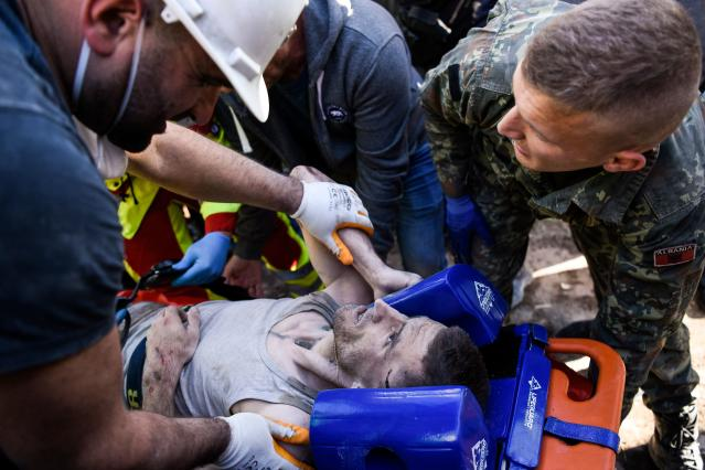 Soldiers and rescue workers carry an injured man found in debris of a collapsed building in Thumane. (Photo: Armend NimaniI/AFP via Getty Images)
