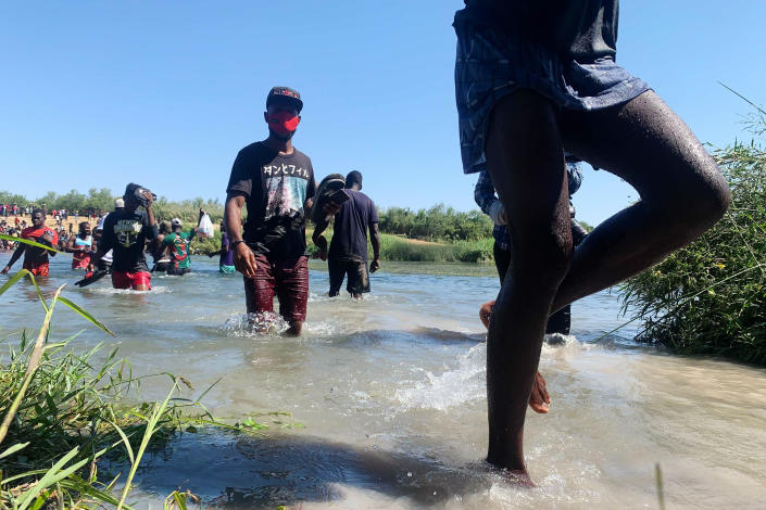 Migrants find an alternate place to cross between Mexico and the United States after access to a dam was closed, Sunday, Sept. 19, 2021, in Ciudad Acuña, Mexico. U.S. officials said that within the next few days, they plan to ramp up expulsion flights for some of the thousands of Haitian migrants who have gathered in the Texas city from across the border in Mexico. (AP Photo/Sarah Blake Morgan)