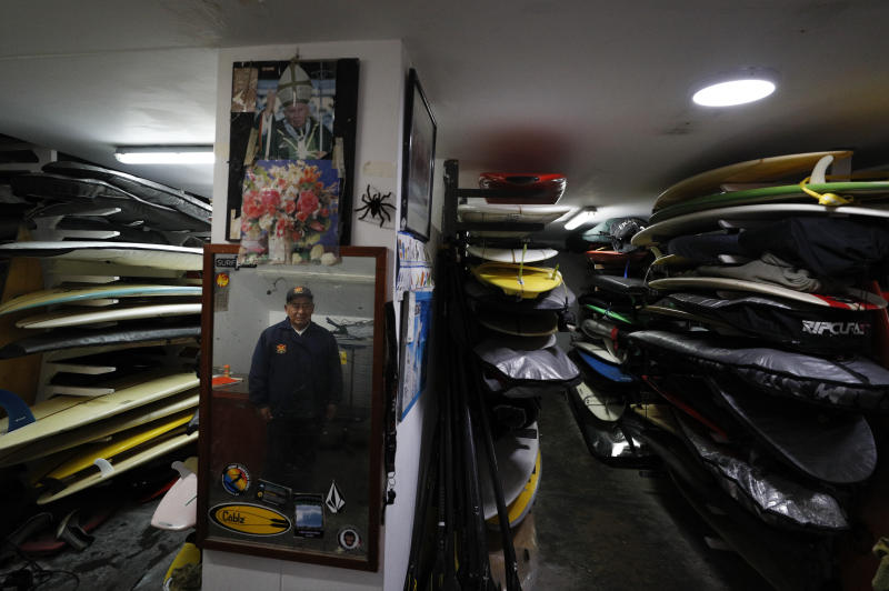 """In this July 26, 2019 photo, Victor """"Mamico"""" Curo, 79, stands amidst the thousands of surfboards he tends in the storage room named after him for his more than 60 years of service, at Club Waikiki in Lima, Peru. Surfing is a way of life in Peru, which has been called the Hawaii of Latin America.(AP Photo/Rebecca Blackwell)"""