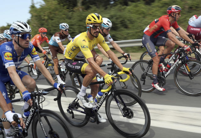 The pack with France's Julian Alaphilippe wearing the overall leader's yellow jersey, center, pedal during the eleventh stage of the Tour de France cycling race over 167 kilometers (103,77 miles) with start in Albi and finish in Toulouse, France, Wednesday, July 17, 2019. (AP Photo/Thibault Camus)