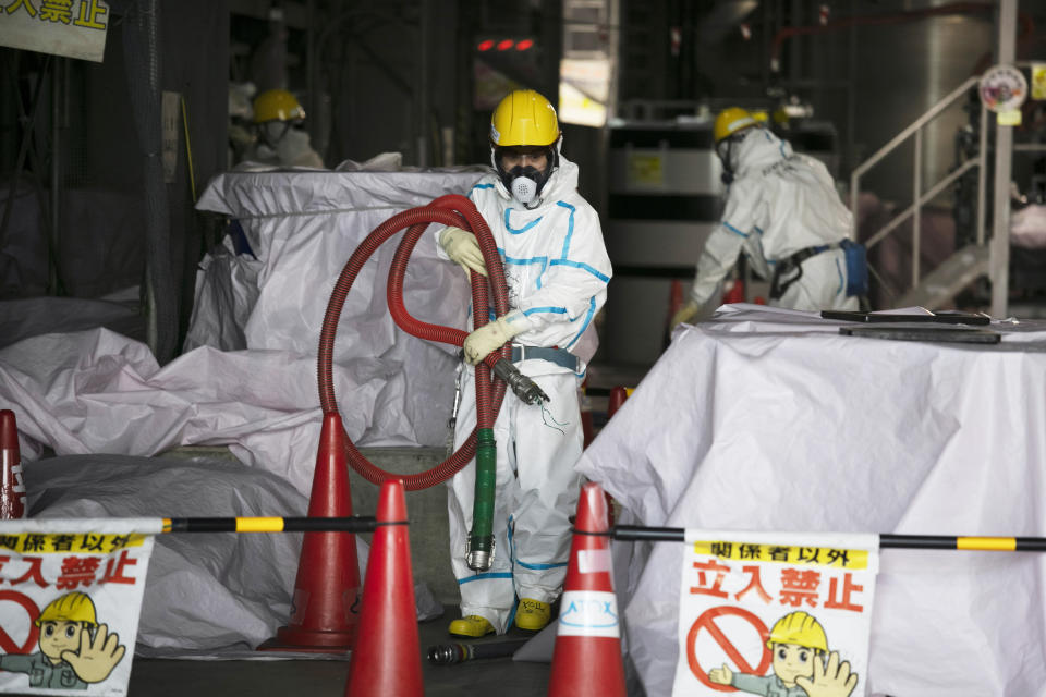 FILE - In this Feb. 12, 2020, file photo, a worker in a hazmat suit carries a hose while working at a water treatment facility at the Fukushima Dai-ichi nuclear power plant in Okuma, Fukushima prefecture, northeastern Japan. The head of the wrecked Fukushima nuclear plant said Tuesday, March 2, 2021 there's no need to extend the current target to finish its decommissioning in 30-40 years despite uncertainties about melted fuel inside the plant's three reactors. (AP Photo/Jae C. Hong, File)