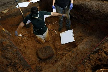 University of South Florida associate professor Christian Wells uses string in an attempt to cut loose a block of dirt and clay containing skull fragments in a grave at the now closed Arthur G. Dozier School for Boys in Marianna, Florida, September 2, 2013. REUTERS/Edmund D. Fountain/Pool