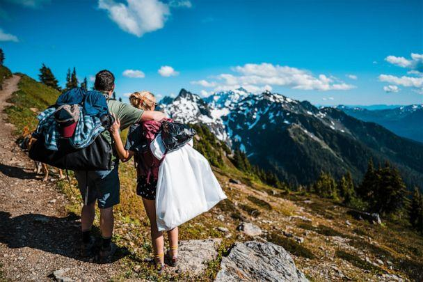 PHOTO: A bride and groom hike with their wedding gown and tux on the way to their adventure elopement. (Thefoxesphotography.com)