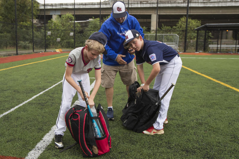 David Fox, center, with his sons Dewey, right. and Jimmy gather their equipment as they wrap up practicing baseball at a baseball field in northeast Washington, Friday, Aug. 23, 2019. David Fox and his wife, Mary Ann, have a rule for their sons, 11-year-old Dewey and 8-year-old Jimmy: They have to play a team sport. The kids get to choose which one. Dewey tried soccer and Jimmy had a go at flag football, but every spring and fall, their first choice is baseball. (AP Photo/Manuel Balce Ceneta)