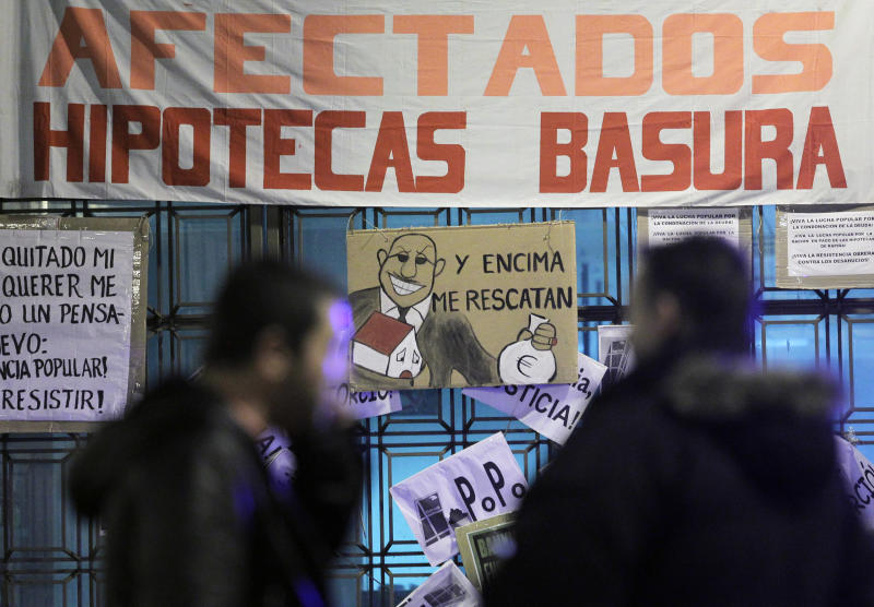 """People walk by a banner reading """"Rubbish mortgage"""" and a drawing of a banker reading """"They even rescued me"""" during a protest against evictions outside Bankia's headquarter in Madrid, Saturday, Nov. 10, 2012. A woman in Spain jumped to her death as bailiffs approached to evict her Friday from her fourth-floor apartment for failing to pay the mortgage, officials said. It was the second apparent suicide linked to evictions, and it further illustrates the dire conditions many Spaniards find themselves in as the country's economy sinks. The government recently created a task force to study how to reduce evictions because of the devastating personal impact of repossessions due to tough Spanish mortgage rules and growing unease among the public on the subject. (AP Photo/Andres Kudacki)"""