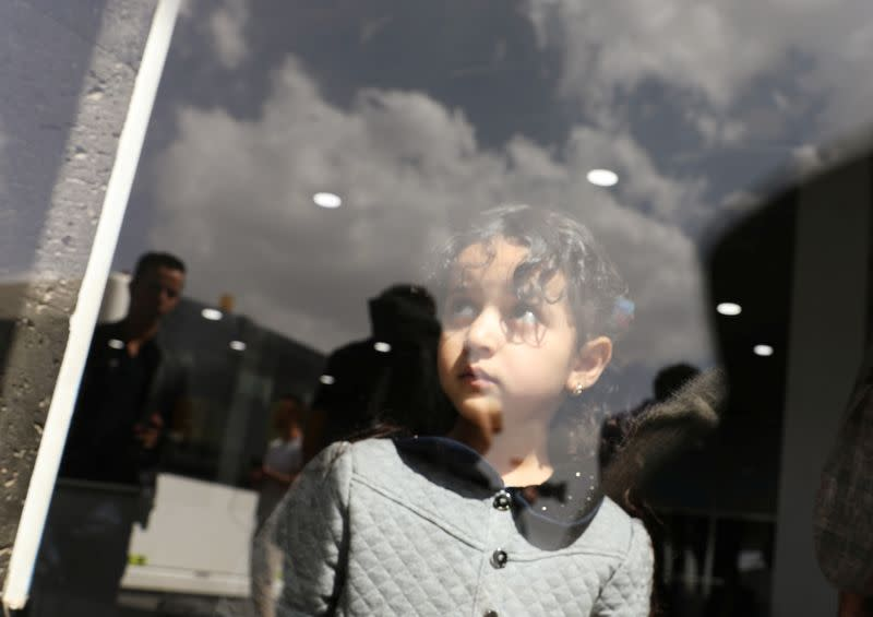 Girl looks from behind a door glass before her boarding on a United Nations plane which will carry her and other patients to Amman, Jordan in the first flight of a medical air bridge from Sanaa airport in Sanaa, Yemen