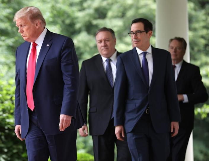"""President Trump, left, Secretary of State Michael R. Pompeo, Treasury Secretary Steven Mnuchin and U.S. Trade Rep. Robert Lighthizer walk to the White House Rose Garden on May 29 before a statement by Trump critical of China. <span class=""""copyright"""">(Getty Images)</span>"""