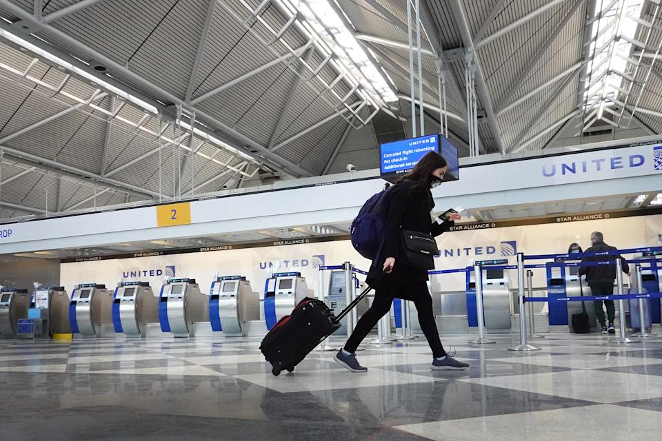 CHICAGO, ILLINOIS - FEBRUARY 05: A passenger arrives for a United Airlines flight at O'Hare International Airport on February 05, 2021 in Chicago, Illinois. United Airlines and American Airlines, two of the nation's largest carriers, are anticipating having to furlough thousands of employees as both companies continue to see a pandemic-related lag in air travel.  (Photo by Scott Olson/Getty Images)