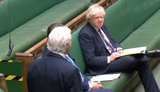 Boris Johnson grimaces at Sir Desmond Swayne during his attack on the government's lockdown. (Parliamentlive.tv)