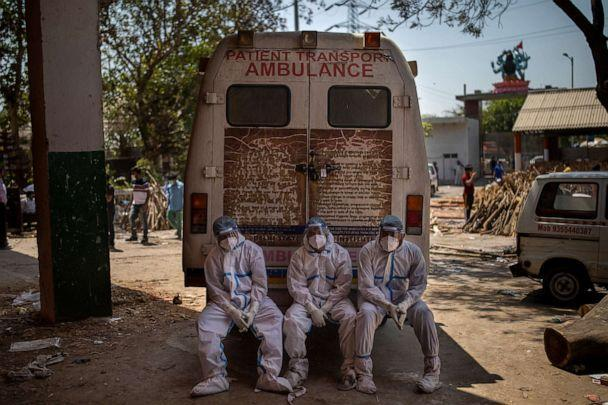 PHOTO: Exhausted workers sit on the rear step of an ambulance in New Delhi, April 24, 2021. (Altaf Qadri/AP)