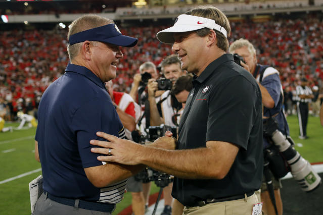 Notre Dame coach Brian Kelly, left, and Georgia coach Kirby Smart, right, shake hands before kickoff of an NCAA football game in Athens, Ga., on Saturday, Sept. 21, 2019. (Joshua L. Jones/Athens Banner-Herald via AP)