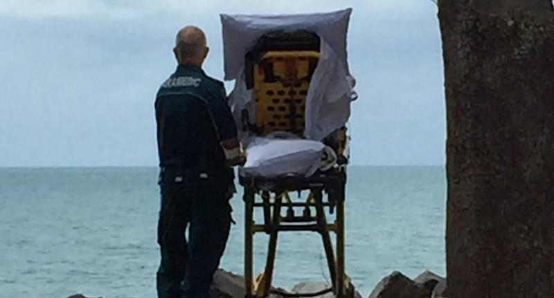 Paramedic Graeme Cooper stands in front of the ocean with a palliative care patient in her bed.