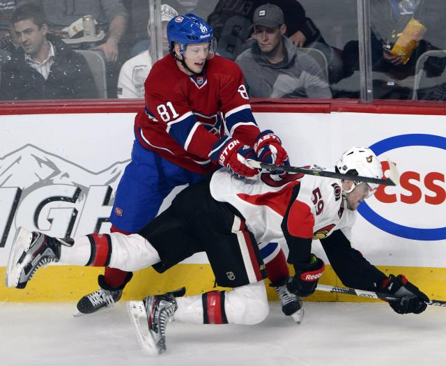 Ottawa Senators' David Dziurzynski is knocked to the ice by Montreal Canadiens Lars Eller, of Denmark, during the second period of an NHL preseason hockey game, Thursday, Sept. 26, 2013. (AP Photo/The Canadian Press, Ryan Remiorz)