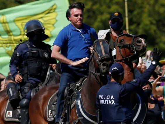 Jair Bolsonaro rides a horse during a demonstration by his supporters in Brasilia, 31 May (REUTERS)