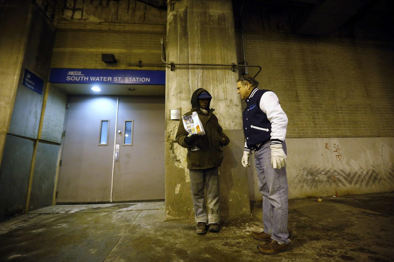 Doctor Patrick Angelo checks on a homeless man under the overpasses on Lower Wacker Drive in Chicago, Illinois, January 7, 2014. Angelo visits the homeless several times a week to hand out food, clothing and blankets to those living on the streets with funding coming from his oral surgery medical practice and profits from his healthcare company. Angelo is in his 13th year doing charity work. Picture taken January 7, 2014. REUTERS/Jim Young (UNITED STATES - Tags: SOCIETY POVERTY)