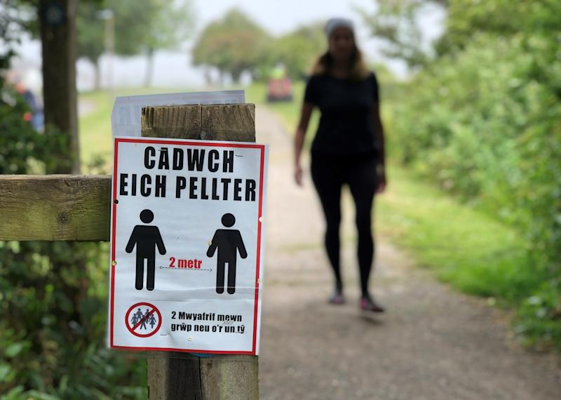 PENARTH, WALES - MAY 20: A social distancing sign written in the Welsh language is seen on a coastal path on May 20, 2020 in Penarth, Wales. The British government has started easing the lockdown it imposed two months ago to curb the spread of Covid-19, abandoning its 'stay at home' slogan in favour of a message to 'be alert', but UK countries have varied in their approaches to relaxing quarantine measures. (Photo by Stu Forster/Getty Images)