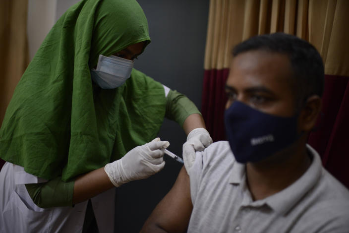 A Bangladeshi man receives a vaccine for COVID-19 at a hospital in Dhaka, Bangladesh, Saturday, May 8, 2021. India's surge in coronavirus cases is having a dangerous effect on neighboring Bangladesh. Health experts warn of imminent vaccine shortages just as the country should be stepping up its vaccination drive, and as more contagious virus variants are beginning to be detected. (AP Photo/Mahmud Hossain Opu)