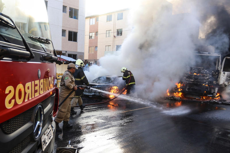 Firefighters put out torched vehicles on a street after attacks in the city of Fortaleza, northeastern Brazil, Thursday, Jan. 3, 2019. Brazil's newly inaugurated government has ordered military police sent to Ceara state following a wave of attacks on banks, public buildings and infrastructure over the past two days, which have hit 15 cities, including the capital. (AP Photo/Alex Gomes/O Povo)