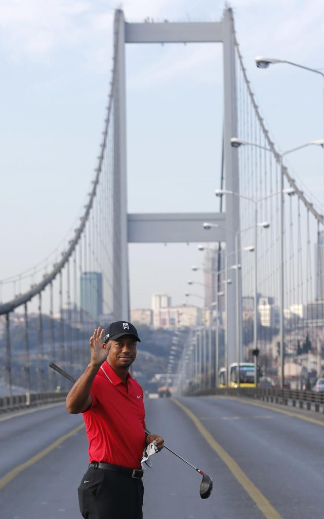 U.S. golfer Tiger Woods greets media members during an event to promote the upcoming Turkish Airlines Open golf tournament, on the Bosphorus Bridge that links the city's European and Asian sides, in Istanbul November 5, 2013. Woods is in Turkey to attend the tournament, which will take place in Antalya, southern Turkey, between November 7 to 10. REUTERS/Murad Sezer (TURKEY - Tags: SPORT GOLF)