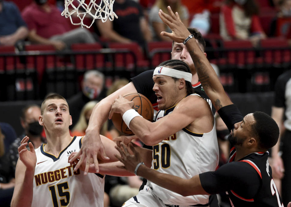 Denver Nuggets forward Aaron Gordon, center, drives to the basket against Portland Trail Blazers center Jusuf Nurkic, top, and forward Norman Powell, right, during the first half of Game 4 of an NBA basketball first-round playoff series in Portland, Ore., Saturday, May 29, 2021. (AP Photo/Steve Dykes)