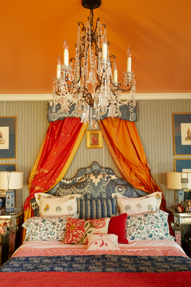"""<p>Designer <a href=""""http://www.michellenussbaumer.com/"""" target=""""_blank"""">Michelle Nussbaumer</a> layers juicy orange hues, exotic prints, and dramatic details with glamorous global style in the master bedroom of her 1950s Dallas mansion. The canopy of Indian saris frames a custom headboard in a <a href=""""https://www.fschumacher.com/"""">Schumacher</a> fabric. A pair of Ceylon et Cie lamps on <a href=""""https://www.jfchen.com/"""" target=""""_blank"""">JF Chen</a> bedside tables flanks the bed. The walls are covered in a fabric from Nussbaumer's line. </p>"""