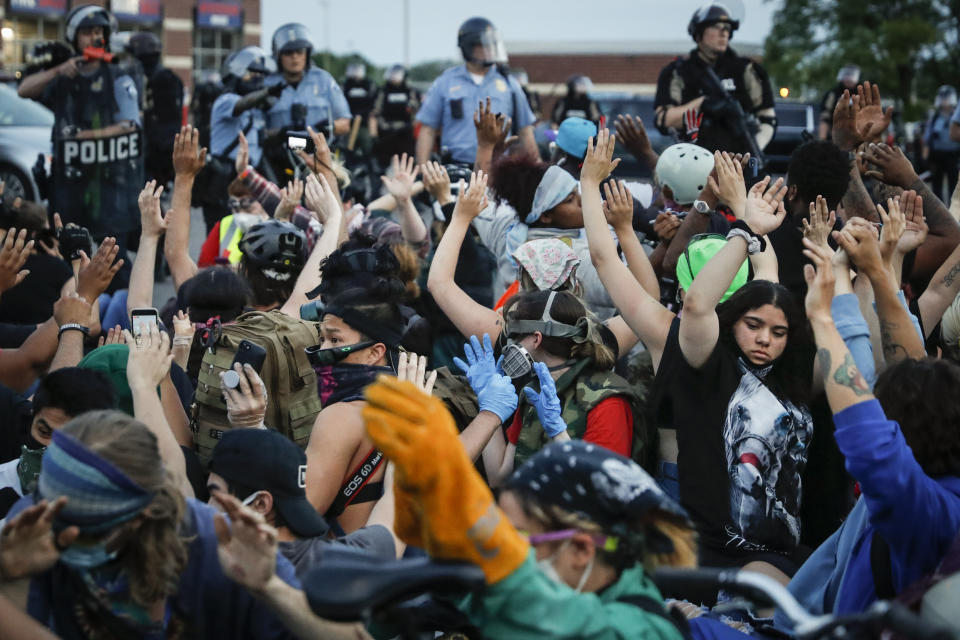 Protesters raise their hands on command from police as they are detained prior to arrest and processing at a gas station on South Washington Street, Sunday, May 31, 2020, in Minneapolis. Protests continued sparked by the death of George Floyd, who died after being restrained by Minneapolis police officers on May 25. (AP Photo/John Minchillo)