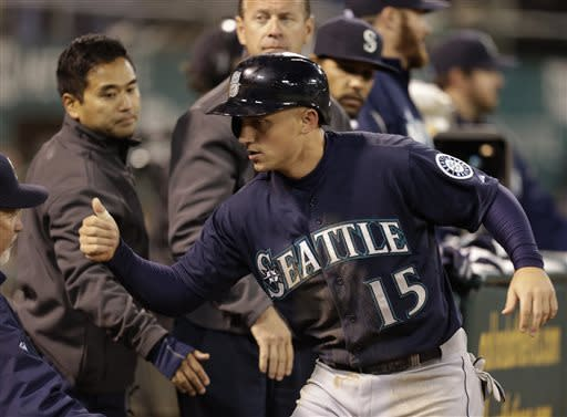 Seattle Mariners' Kyle Seager (15) is congratulated after scoring against the Oakland Athletics in the seventh inning of a baseball game Tuesday, April 2, 2013, in Oakland, Calif. Seager scored when Athletics pitcher Ryan Cook walked Mariners' Justin Smoak with the bases loaded. (AP Photo/Ben Margot)