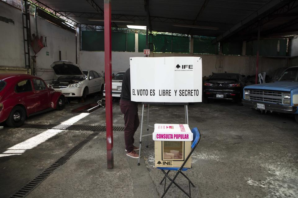 A man casts his during in a non-binding referendum on whether Mexican ex-presidents should be tried for any illegal acts during their time in office, in Mexico City, Sunday, August 1, 2021. (AP Photo/Christian Palma)