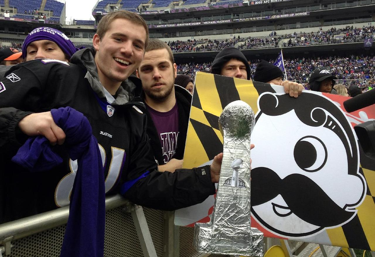 Sam Muffoletto, 21, and Phil Luzi, 21, hold up signs and a home-made Super Bowl trophy as they wait for the start of Baltimore's celebration for the Super Bowl champion Baltimore Ravens at Ravens stadium on Tuesday, Feb. 5, 2013. Officials expect about 100,000 people to attend the events. (AP Photo/Alex Dominguez)