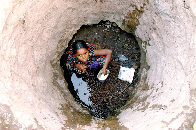 In 2003 in Djibouti, a girl collects water from the bottom of a well in a rural area in Padjourah District. Drought has depleted much of the water supply.