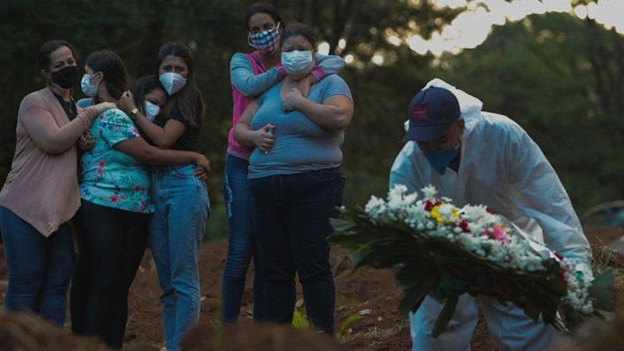 Relatives of coronavirus victims mourn when a loved one is buried at Vila Formosa Cemetery in Sao Paulo, Brazil, on March 31, 2021.