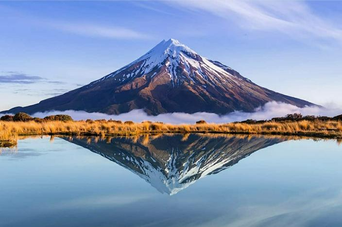 'Mount Taranaki, New Zealand' by @superthijs shows Mount Taranaki  in New Zeland reflected in a lake.