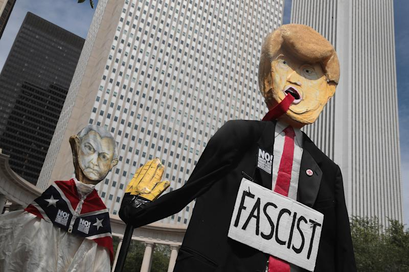 Demonstrators in Chicago protesting the alt-right and mourning Charlottesville, Virginia, victims carry puppets of President Donald Trump and U.S. Attorney General Jeff Sessionson Aug. 13. (Scott Olson via Getty Images)