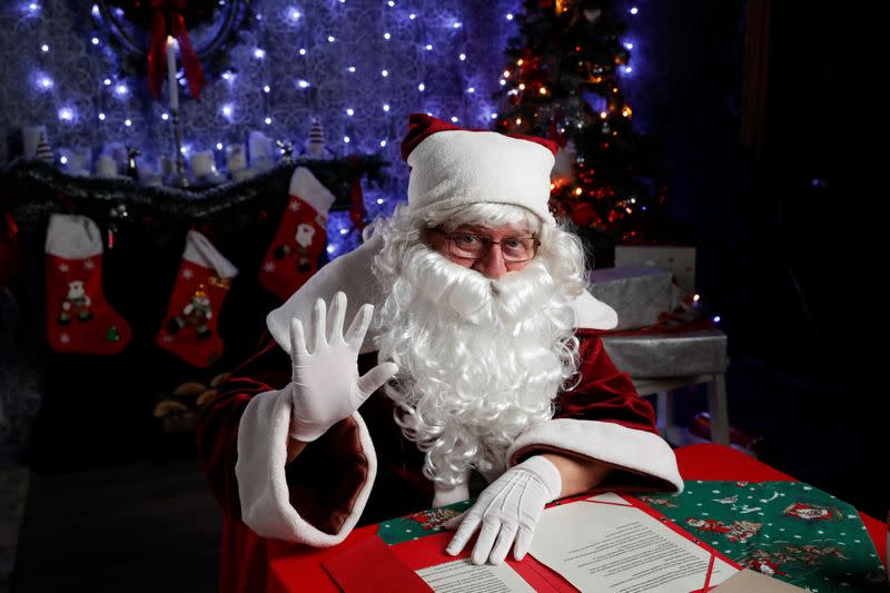 Nemes, dressed as Santa, waves as he interacts with children by video in a photo studio, amid the COVID-19 outbreak in Budapest