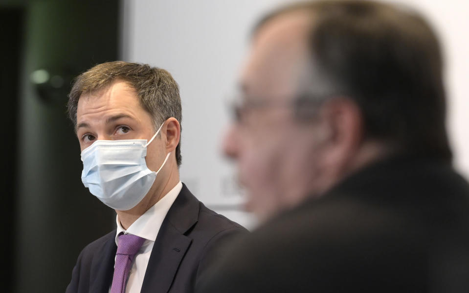 Belgium's Prime Minister Alexander De Croo, left, speaks during a media conference at the prime minister's office in Brussels, Monday, Feb. 22, 2021.The government on Monday presented scientific projections of the spread of the COVID-19 pandemic in Belgium, indicating it would be very risky to extensively loosen the current restrictions over the coming weeks. (Philip Reynaers, Pool via AP)