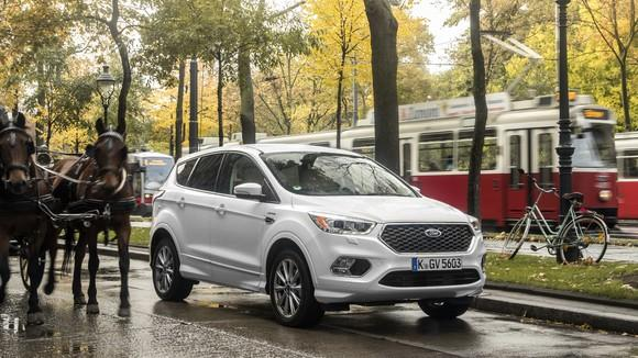 A white Ford Kuga, a compact SUV, on a city street.