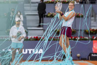 Aryna Sabalenka of Belarus, right, holds a trophy after winning the women's final match against Australia's Ashleigh Barty at the Mutua Madrid Open tennis tournament in Madrid, Spain, Saturday, May 8, 2021. (AP Photo/Bernat Armangue)