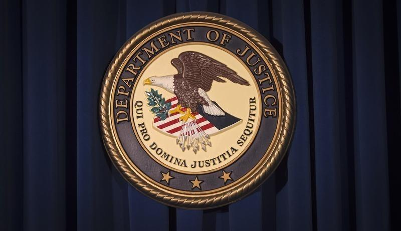 The DOJ logo is pictured on a wall after a news conference in New York