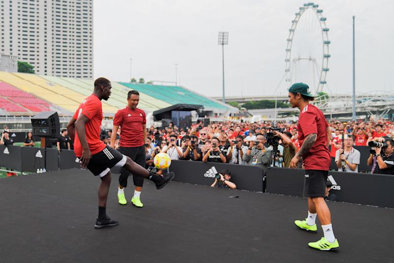 Manchester United's Paul Pogba (left) attempting to juggle a sepak takraw ball as Singapore football great Fandi Ahmad (second from left) watches on in an adidas meet-and-greet fan session at The Float@Marina Bay. (PHOTO: adidas)