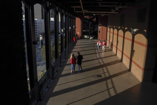 Fans arrive to Busch Stadium for Game 1 of the National League Championship Series baseball game between the St. Louis Cardinals and the Washington Nationals Friday, Oct. 11, 2019, in St. Louis. (AP Photo/Charlie Riedel)