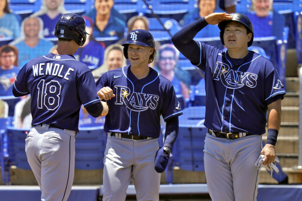 Tampa Bay Rays' Joey Wendle, left, shakes hands with Taylor Walls, center, as Ji-Man Choi pretends to see how far the ball went after Wendle hit a grand slam off Toronto Blue Jays starting pitcher Trent Thornton during the first inning of a baseball game Monday, May 24, 2021, in Dunedin, Fla. (AP Photo/Chris O'Meara)