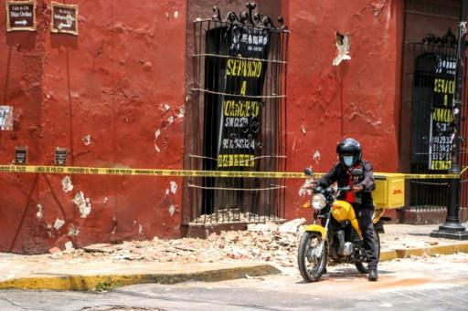 A motorcyclist rides past a damaged building after a quake in Oaxaca, Mexico