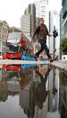 FILE PHOTO: A man jumps over a puddle in the City of London financial district during the morning rush hour