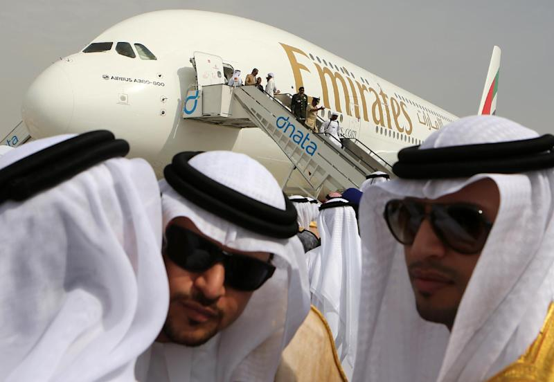 Emirati officials greet each other in front of an Emirates Airbus A380 on display during the opening day of the Dubai Airshow in Dubai, United Arab Emirates, Sunday Nov. 17, 2013. The Dubai Airshow is seen as an increasingly important barometer on the state of the industry and the rising roles of the big-spending Gulf carriers Etihad, Qatar Airways and Emirates as they compete for routes and critical stopover traffic between Asia and Europe and the Americas. (AP Photo/Kamran Jebreili)